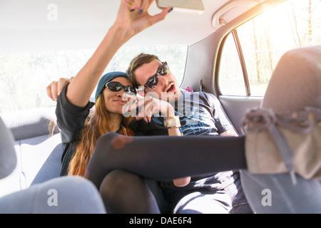 Couple sur la banquette arrière de voitures de photographier eux-mêmes Banque D'Images