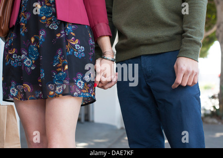 Young couple holding hands, mid section Banque D'Images
