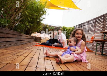 Fille avec sœur bébé assis sur les genoux, les parents en arrière-plan Banque D'Images
