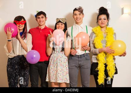Les amis à une fête avec des ballons, studio shot Banque D'Images