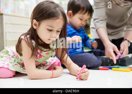 La mère et deux enfants dessin dans jardin Banque D'Images
