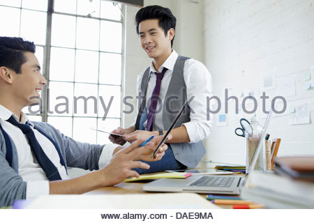 Deux jeunes hommes talking in office Banque D'Images
