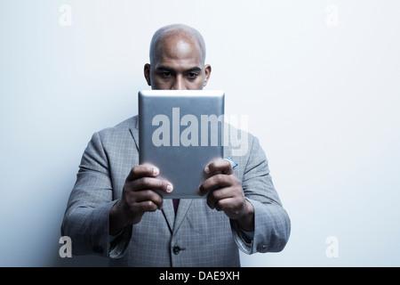 Studio portrait of businessman holding up digital tablet