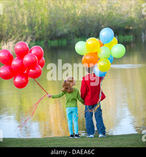 Brother and sister holding balloons in park Banque D'Images