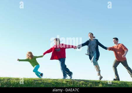 Les parents et deux enfants courir et tenir la main