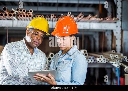 L'homme et de la femme dans l'entrepôt looking at digital tablet Banque D'Images