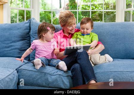 Grand-mère et ses petits-enfants sur canapé looking at digital tablet Banque D'Images