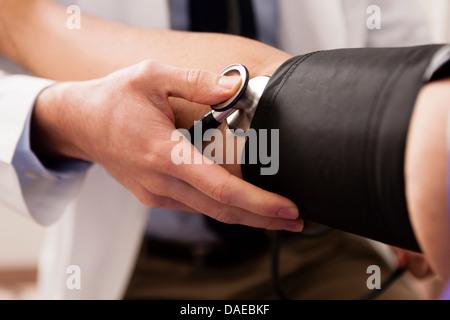 Young doctor with stethoscope et la pression artérielle du brassard sur le patient, Close up Banque D'Images