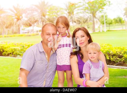 Portrait of cute famille en passant du temps ensemble dans le parc, les jeunes parents heureux avec deux adorables Banque D'Images