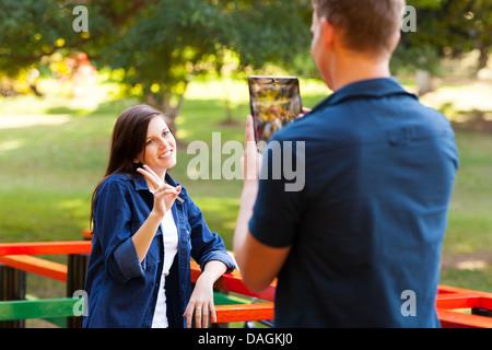 Adolescent de prendre photo de sa petite amie using tablet computer Banque D'Images