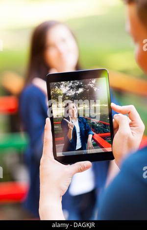 Teen boy taking photos de sa petite amie à l'aide d'un ordinateur tablette Banque D'Images