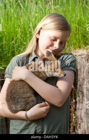 Le renard roux (Vulpes vulpes), fille d'un mineur orphelin sur le bras d'être upbrought à la main, Allemagne Banque D'Images