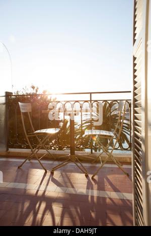 Deux chaises et une table sur un tarrace dans le soleil, les palmiers. Table romantique pour deux sur une terrasse Banque D'Images