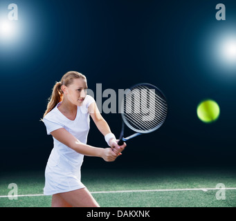Tennis player hitting ball on court Banque D'Images