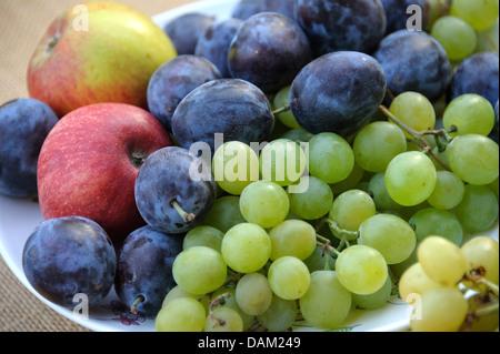 Les prunes, pommes et raisins sur une plaque Banque D'Images
