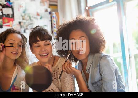 Les femmes appliquant le maquillage dans la chambre Banque D'Images