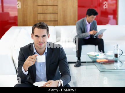 Businessman having cup of coffee in office Banque D'Images