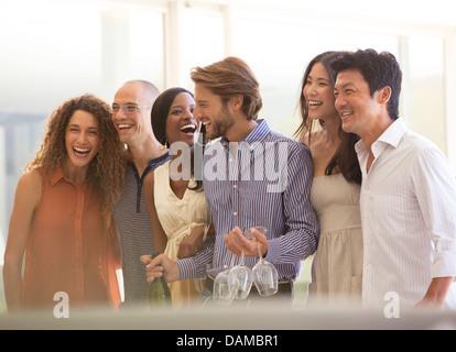 Les amis rient ensemble at party Banque D'Images