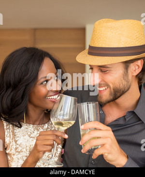 Couple toasting each other indoors Banque D'Images