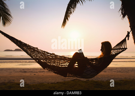 Silhouette of woman relaxing in hammock sur la plage Banque D'Images
