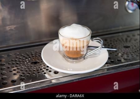 Style Barista café latte mousseux dans un verre tasse et soucoupe blanc assis sur une machine à café Banque D'Images