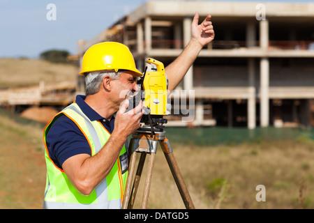 Géomètre principal en conversation sur talkie walkie at construction site Banque D'Images