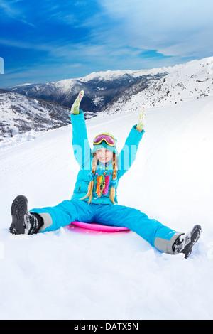Happy girl faisant glisser en descente sur traîneau avec ses mains levées, le port de masque de ski, avec les montagnes Banque D'Images