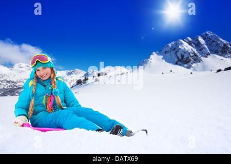 Happy girl sitting on sled, le port de masque de ski, avec les montagnes en arrière-plan Banque D'Images