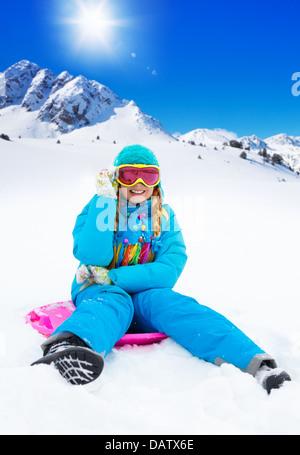 Portrait of happy girl sitting on sled, le port de masque de ski, avec les montagnes en arrière-plan Banque D'Images