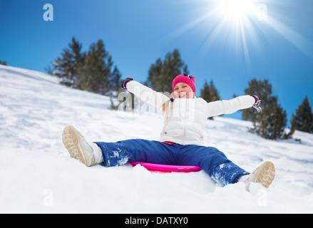 Happy girl sitting on traîneau avec ses mains levées, le port de masque de ski, dans les montagnes Banque D'Images