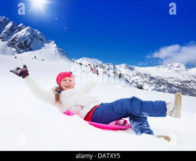 Happy girl faisant glisser sur un traîneau avec ses mains levées, le port de masque de ski, dans les montagnes Banque D'Images