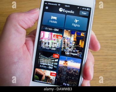 En utilisant app Expedia pour réserver des voyages sur smartphone iPhone 5 blanc Banque D'Images