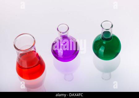 Verrerie de laboratoire avec des liquides de différentes couleurs sur fond blanc. Banque D'Images