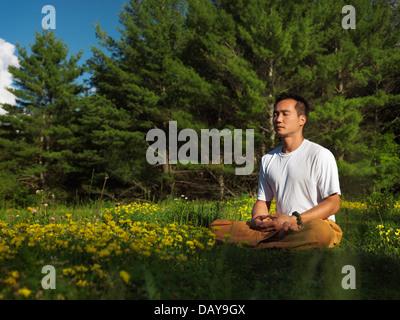 Toronto l'école Shaolin Dao formateur méditer en plein air au lever du soleil, dans la nature, assis en tailleur Banque D'Images