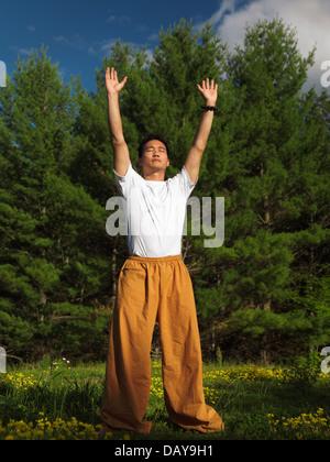 Portrait d'un homme pratiquant la méditation Qi Gong lever du soleil dans la nature. Le Qigong, chi kung, chi gung. Banque D'Images