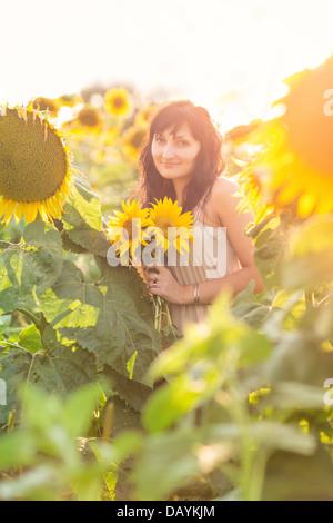 Belle jeune femme avec un bouquet de tournesols dans le domaine Banque D'Images