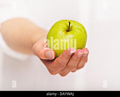 La main de femme donnant une pomme verte