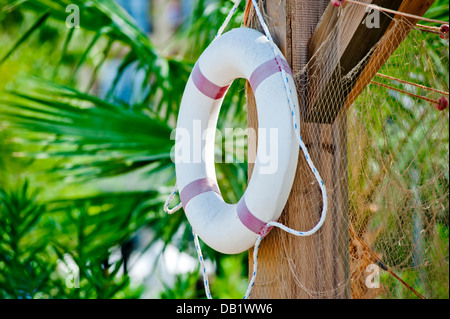 White life preserver hanging on a wooden post Banque D'Images