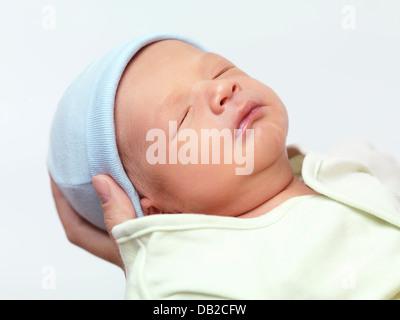 Closeup portrait of a cute newborn baby boy in mother's hands isolé sur fond blanc Banque D'Images