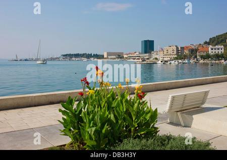 Une vue panoramique de la Riva Waterfront à Split, Croatie avec des fleurs colorées, un banc et voiliers du port de plaisance.