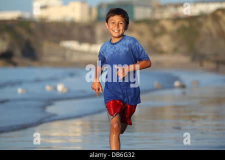 Jeune garçon joue et s'exécute dans le surf le long d'une plage anglaise près de Sunset Banque D'Images