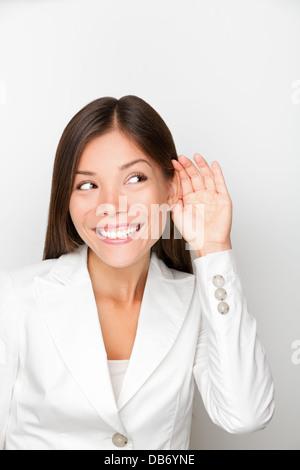 Femme d'affaires à l'écoute avec une oreille à la main concept. Businesswoman smiling happy écouter quelque chose Banque D'Images