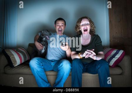 Couple d'âge moyen et de chien à regarder la télévision de rire Banque D'Images
