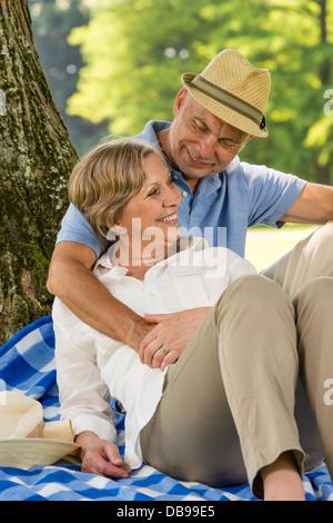Professionnels personnes âgées femme et mari hugging in park Banque D'Images