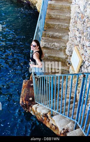Smiling Brunette Woman Standing At un garde-corps bleu à côté de la mer Banque D'Images