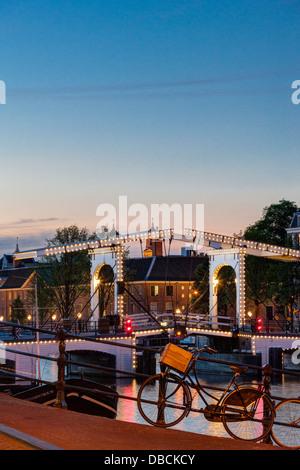 Amsterdam Magere Brug, Skinny Bridge, sur la rivière Amstel et Musée de l'Ermitage à la tombée de nuit soir en été Banque D'Images