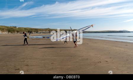 Des personnes qui exploitent des kayaks hors de l'eau après le canoë à Pembrokeshire Wales UK Whitesands Bay Banque D'Images