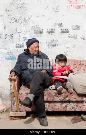 Qijiawan, Nanjing, Chine. Grand-père et sa petite-fille assise sur un canapé dans la rue. Banque D'Images