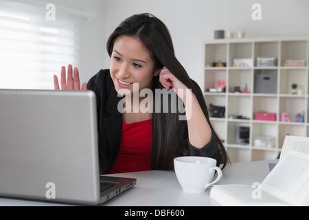 Mixed Race businesswoman using laptop