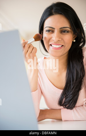 Indian woman applying makeup in mirror Banque D'Images